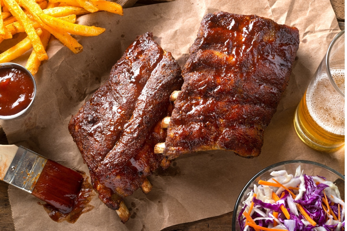 top down view of 2 slabs of 3 2 1 ribs brushed with barbecue sauce and served with fries slaw and beer