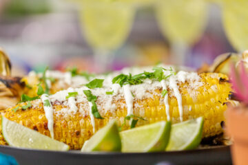 Grilled Mexican street corn Elote slathered with cream and garnished with chili pepper, cilantro and fresh lime.