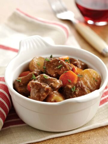 Instant Pot beef stew in a bowl showing chunks of beef, potatoes, and carrots.