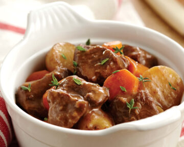 Instant Pot beef stew in a bowl showing chunks of beef, potatoes, and carrots.r