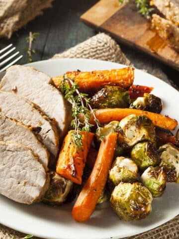 Instant Pot Pork Roast carved and served with roasted carrrots and brussels sprouts.