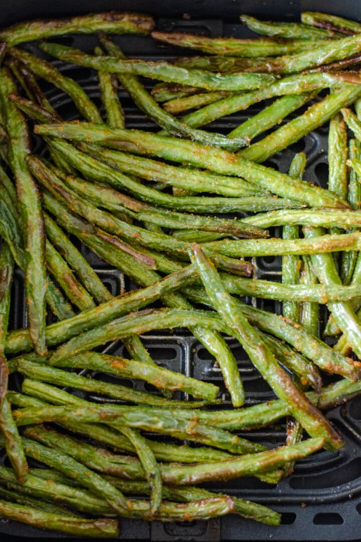 Top down view of air fried green beans in the air fryer basket.