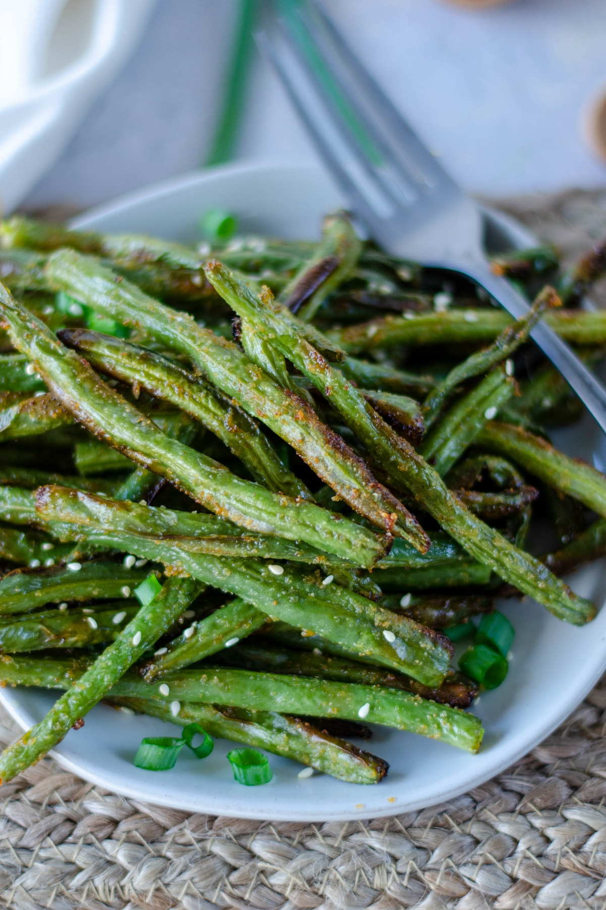 Crispy air fried green beans garnished and served on a white plate on a light woven dinner mat. For on the plate.