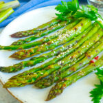 Air Fryer Asparagus arranged on a white plate garnished with sesame seeds.