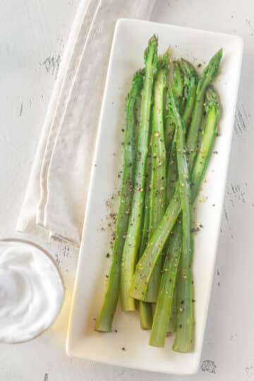 Air fryer asparagus on a rectangular white plate with a white sauce.