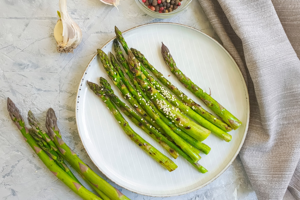 Air fryer asparagus served on a white plate with fresh garlic and freshly ground black pepper on the side