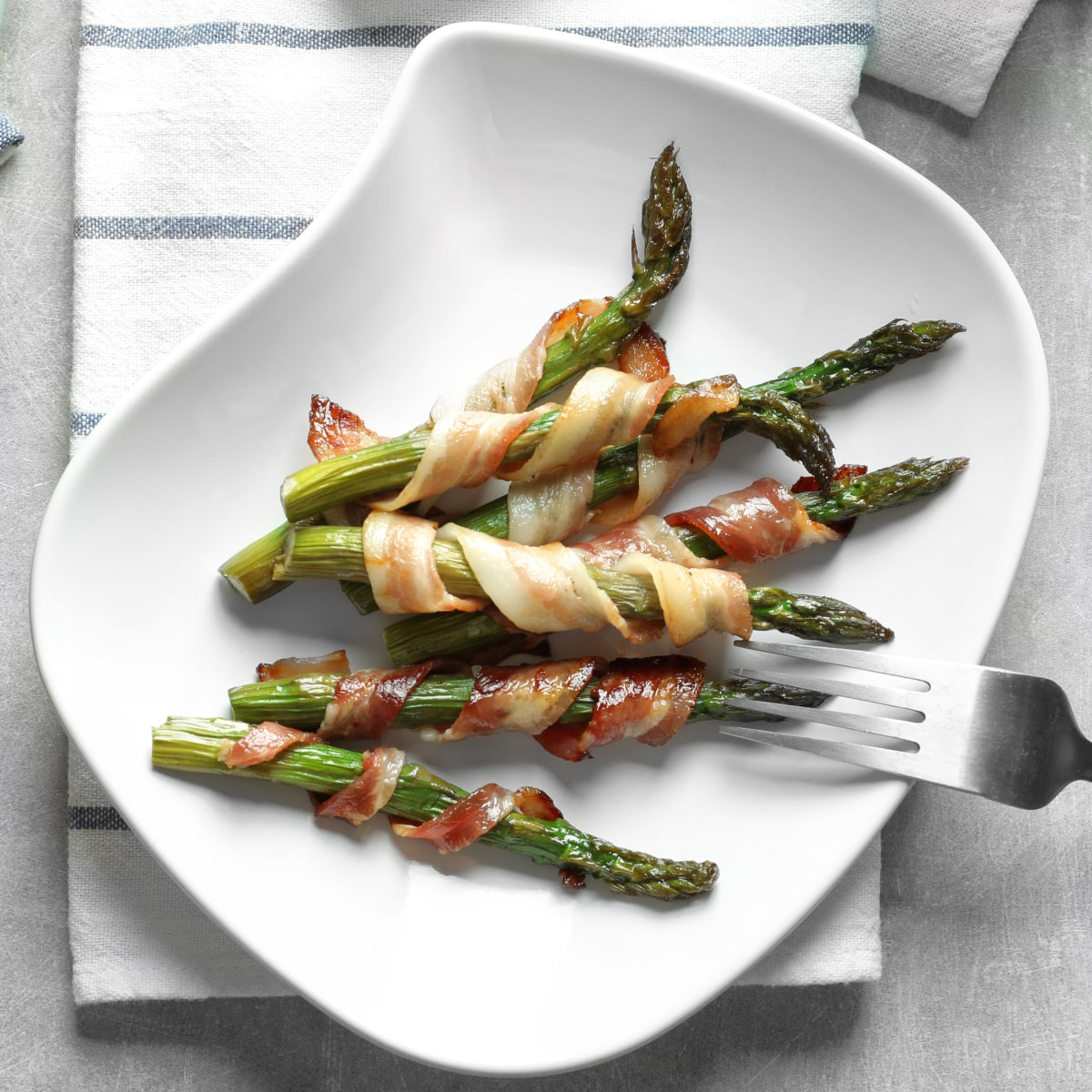 Air fryer asparagus wrapped in bacon and served on a white plate