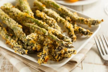 Closeup of air fryer asparagus fries on a white platter