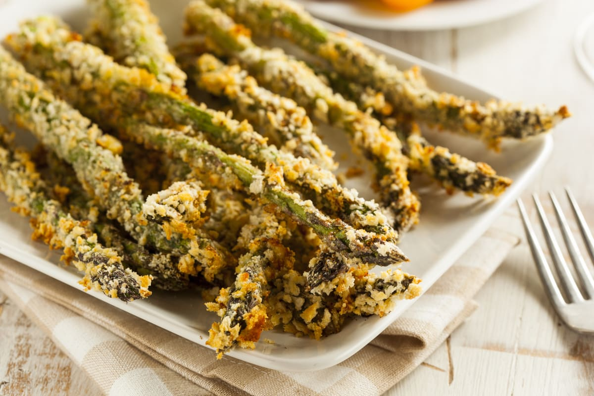 Closeup of air fryer asparagus fries on a white platter
