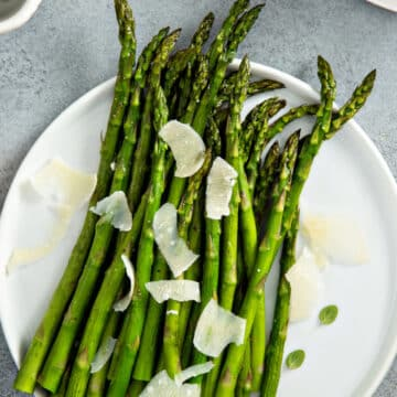 Air fryer asparagus on a white plate with shaved parmesan cheese