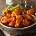 Air fryer chicken wings served in a bowl with celery sticks and blue cheese dressing on the side.