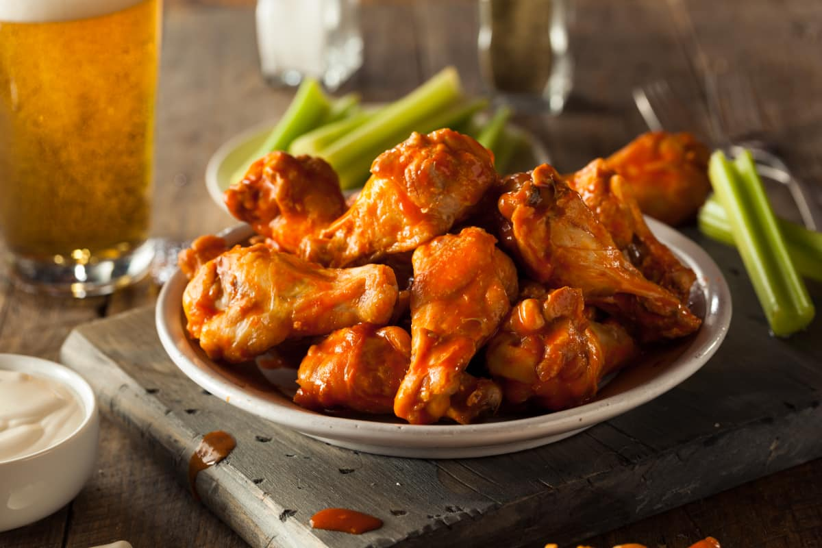 Air fryer chicken wings served with celery, bleu cheese dipping sauce and a cold draft beer.