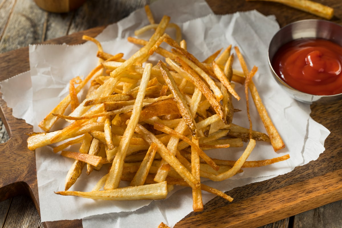 air fryer frozen French fries cooked crispy and arranged on parchment paper with ketchup on the side