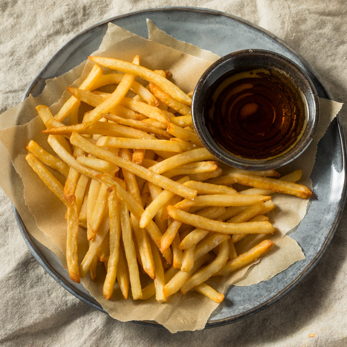 air fryer french fries on a blue stone plate with malt vinegar for dipping