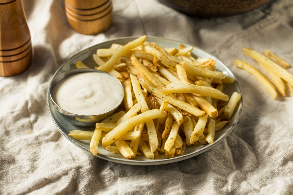 air fryer frozen French fries on a plate with ranch dressing