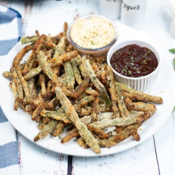 air fryer breaded green beans arranged on a plate with 2 types of dips