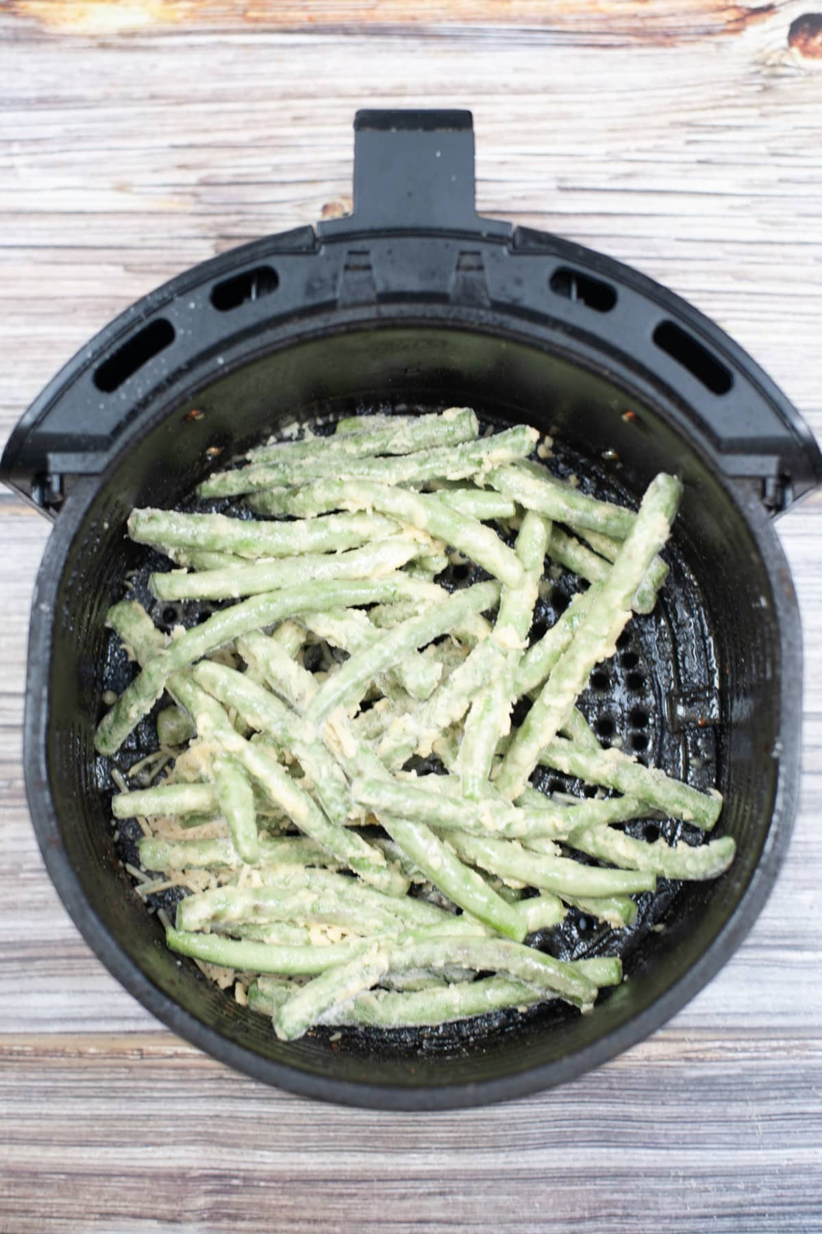 air fryer green beans arranged in the air fryer before cooking
