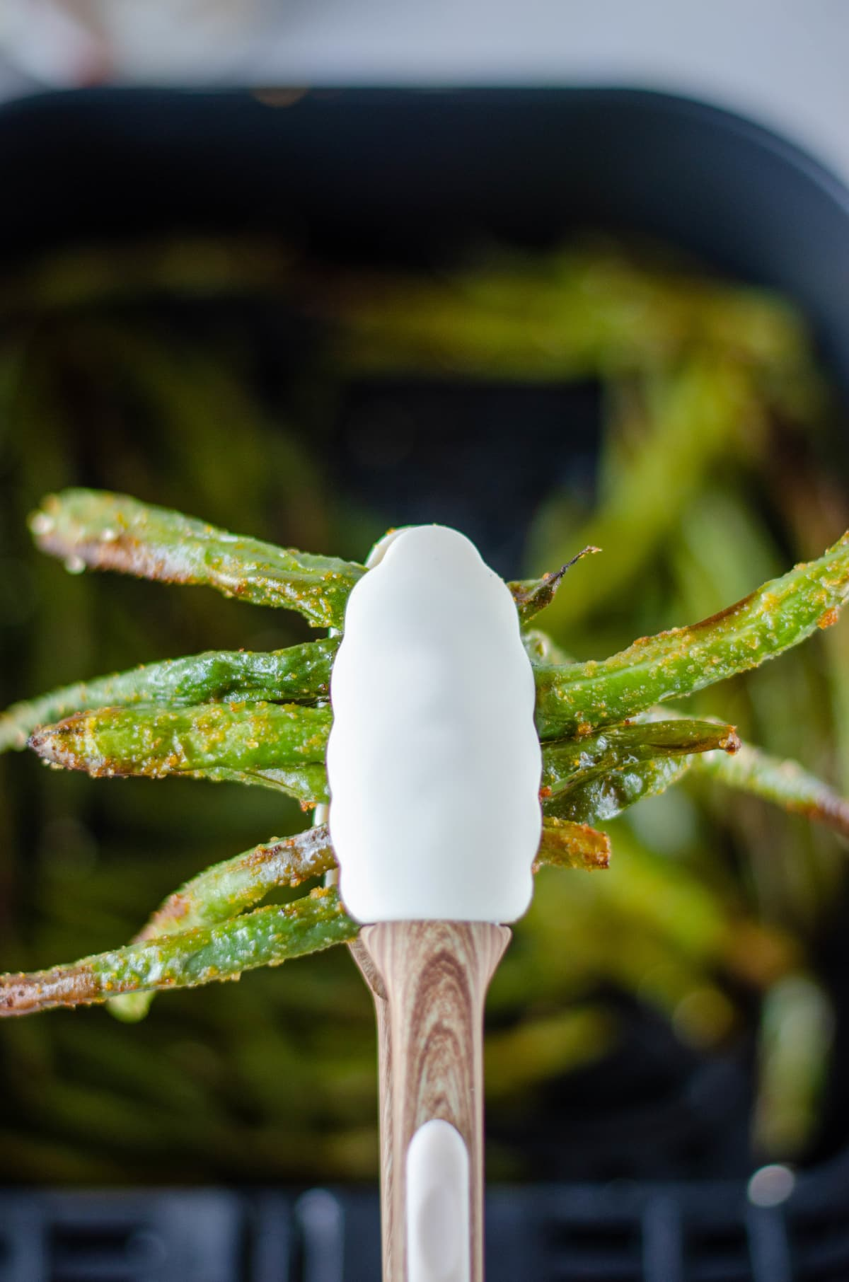 air fryer green beans held upright with a white spatula