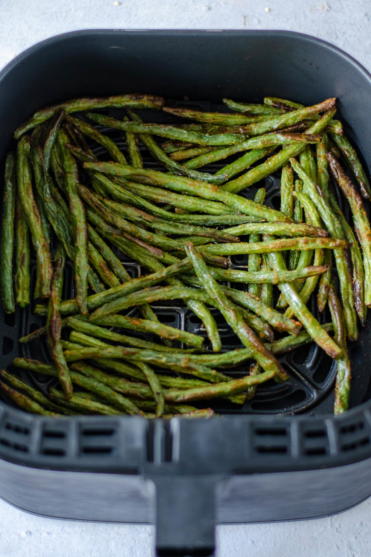roasted green beans in the air fryer basket