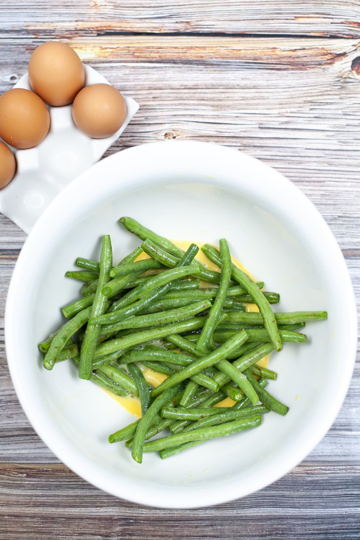 green beans getting dipped in an egg and garlic wash