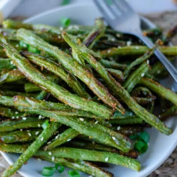 top down view of crispy air fryer green beans on a white plate