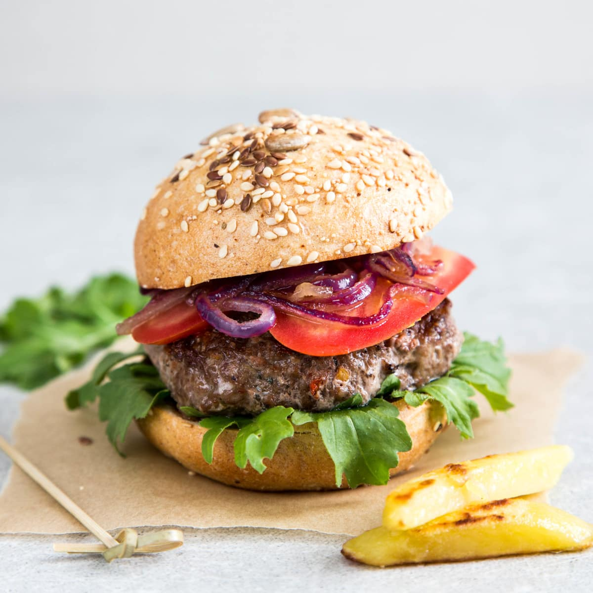 Fresh or frozen air fryer hamburgers from scratch topped with tomatoes, red onions, and lettuce served on a hamburger bun. A couple of air fryer French fries are in the foreground