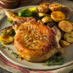 air fryer pork chops served on a plate with roasted potatoes and roasted brussels sprouts