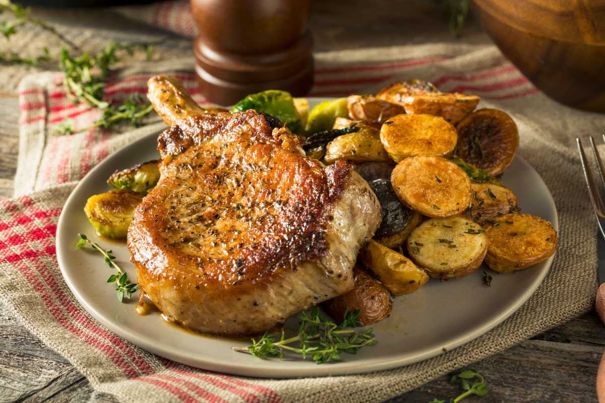 golden pork chop on a plate with roasted veggies