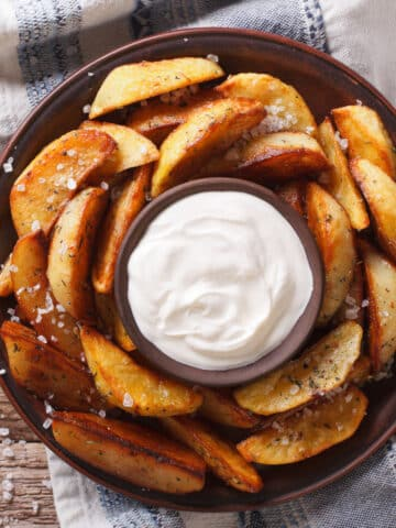air fryer potato wedges on a plate with dip in the middle. Top down view.
