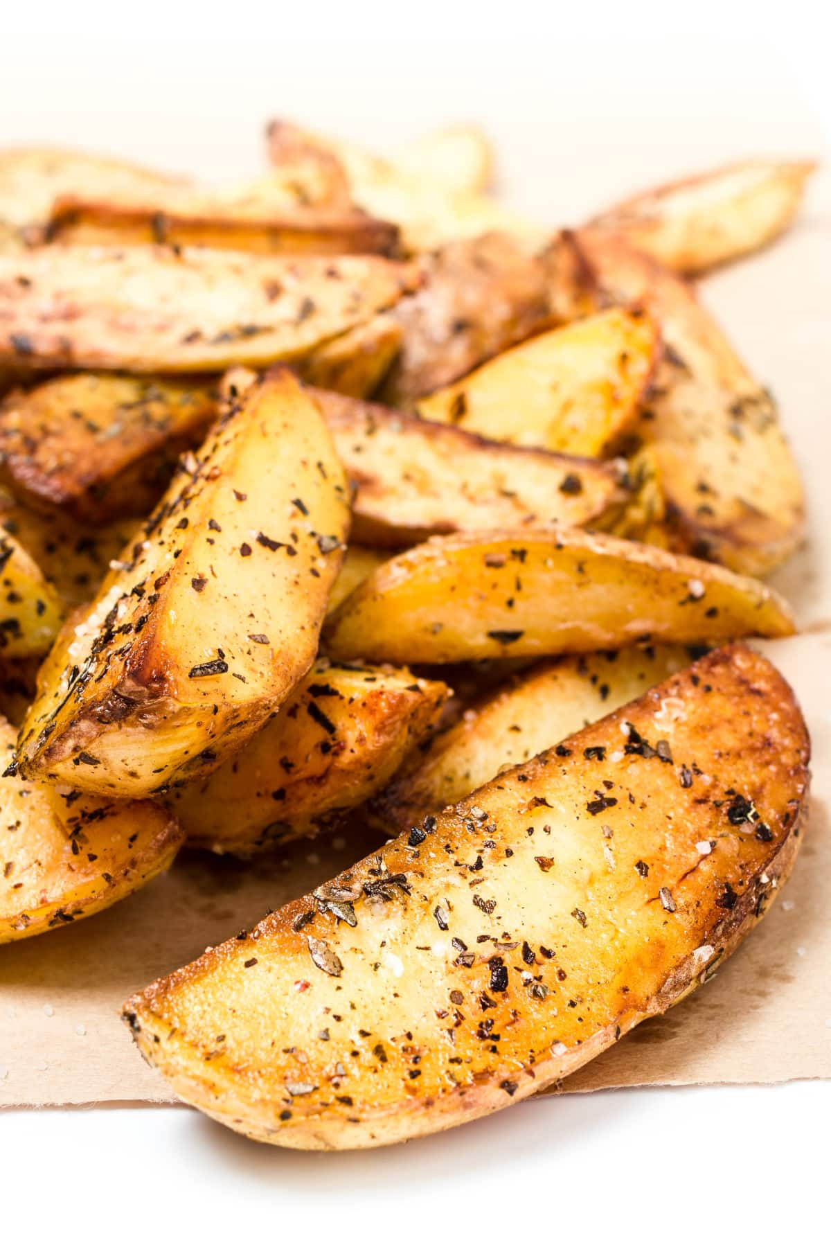 closeup of air fryer potato wedges with seasoning and golden crispy edges