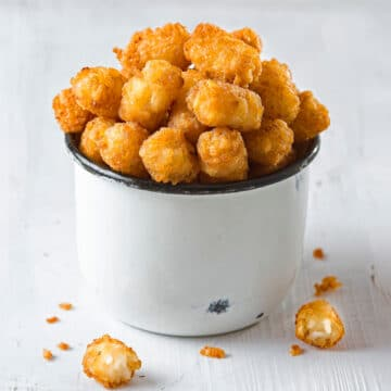 Air fryer tater tots in a little white metal bucket with a couple on the table.