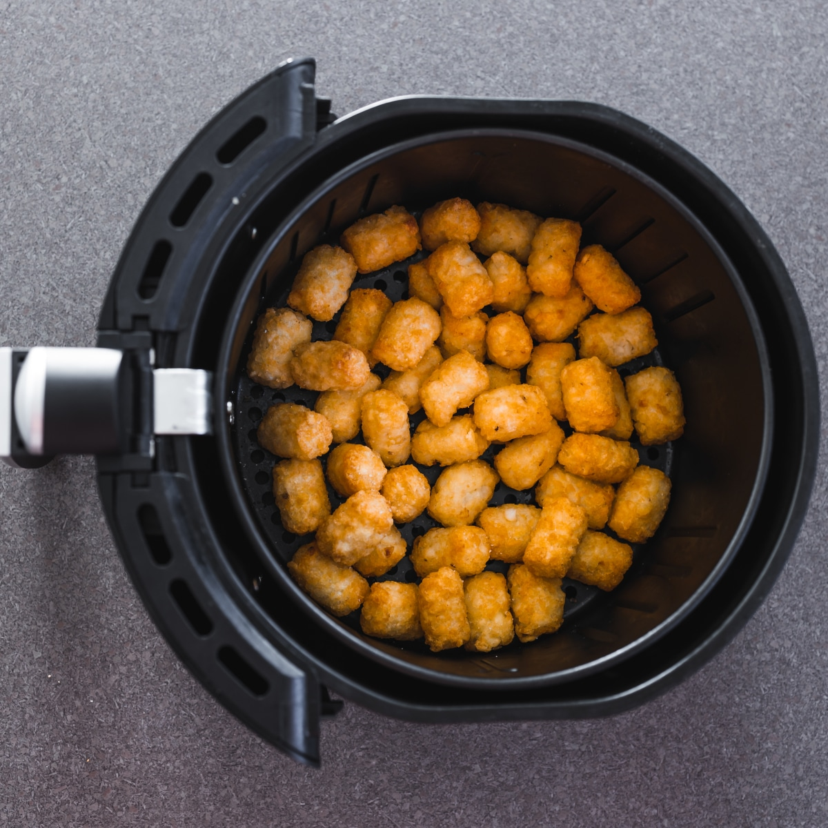 Tater tots in air fryer basket top down view.