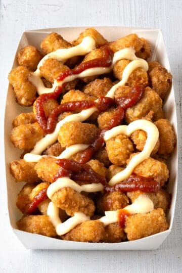Air fryer tater tots in a paper tray drizzled with ketchup and dressing.