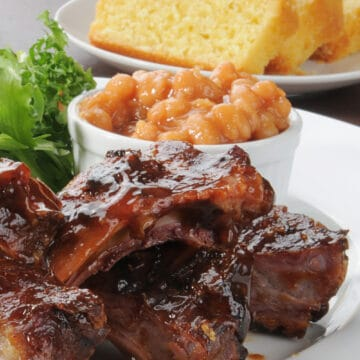 Amazing BBQ Ribs in the Oven on a plate with baked beans and toasted bread.