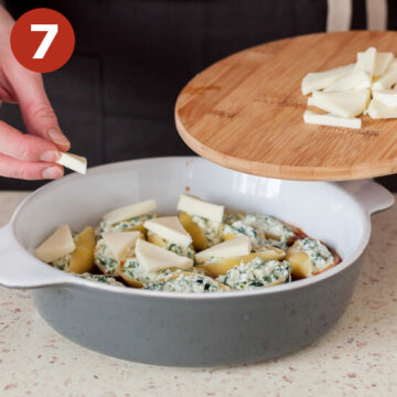 Arranging cheese on top of the stuffed shells before baking