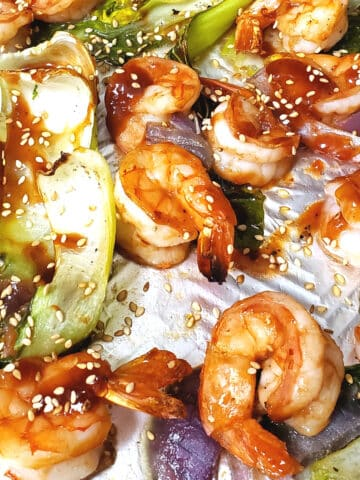 Baked Shrimp with bok choy on a sheet pan seasoned with sambal oelek and toasted sesame seeds.
