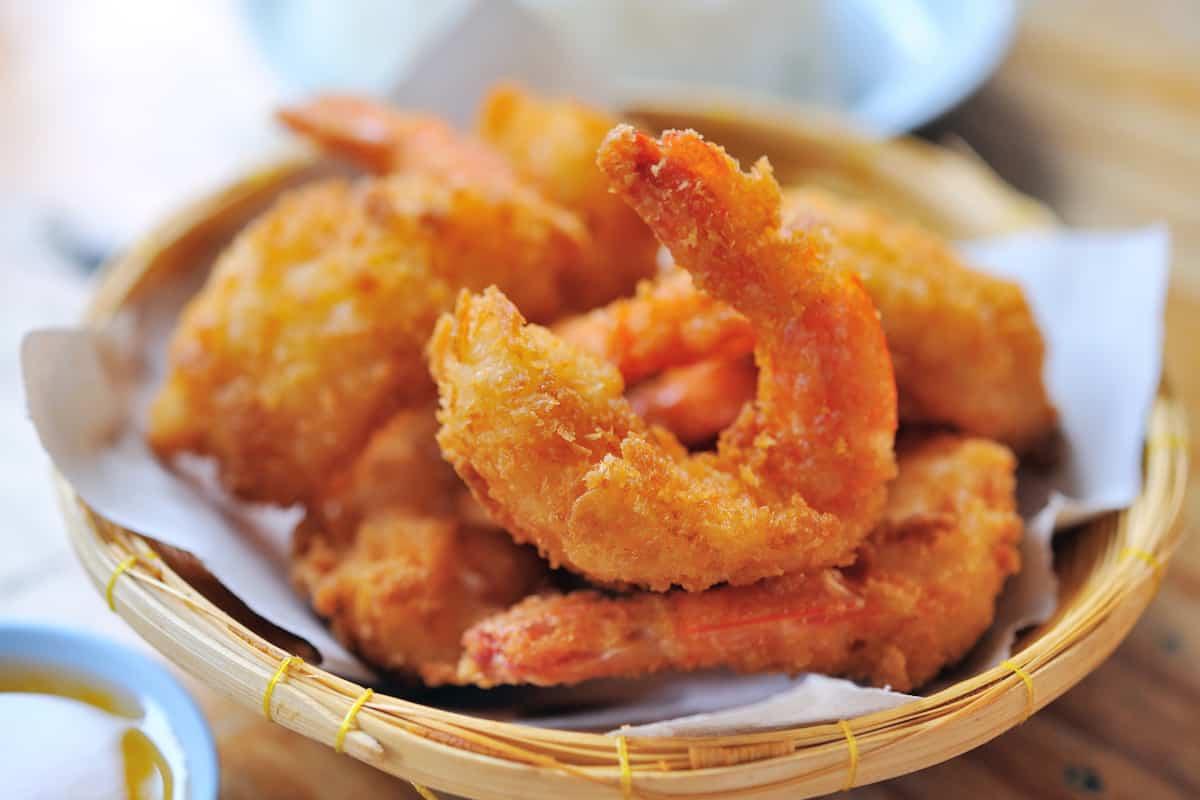 Crispy air fryer shrimp served in a woven basket.