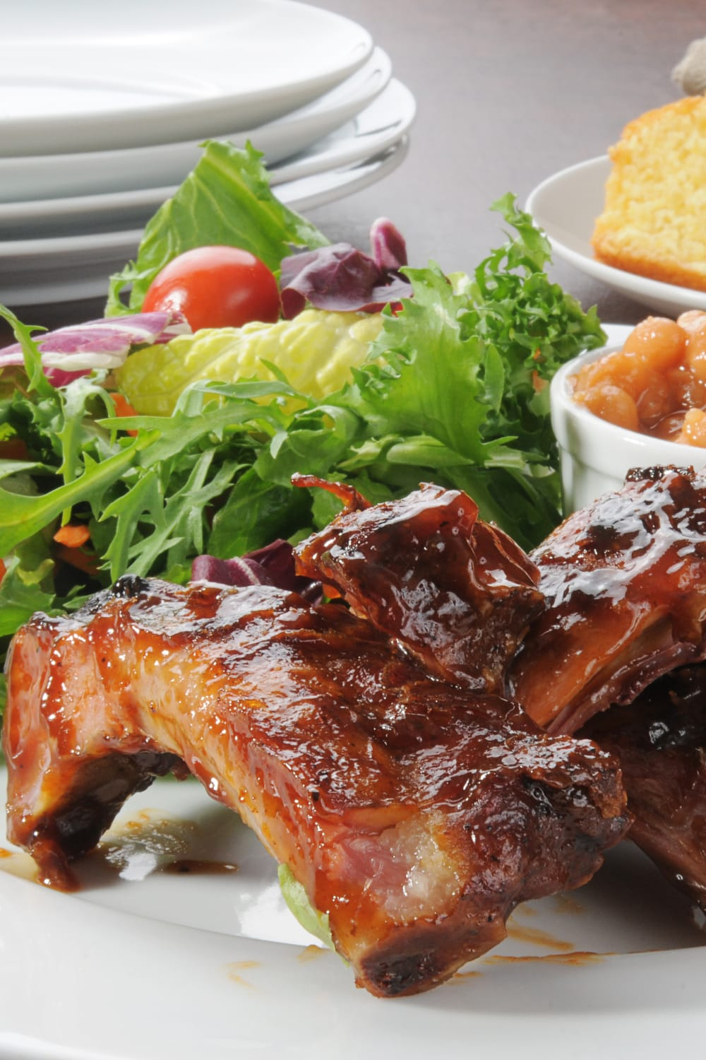 Oven baked bbq ribs served with salad, baked beans, and cornbread. Carved BBQ ribs are slathered in a rich BBQ sauce.