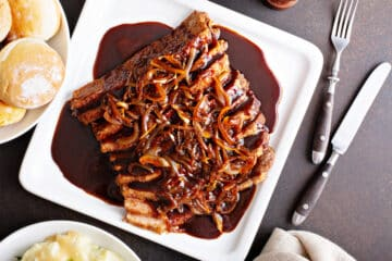 beef brisket top down view served on a white square plate with caramelized onions arrange on top