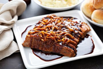 beef brisket served on a white plate with caramelized onions on arranged over the top