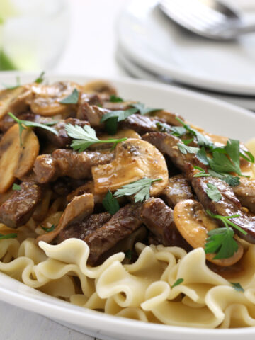 beef and mushroom stroganoff over noodles served on a white plate