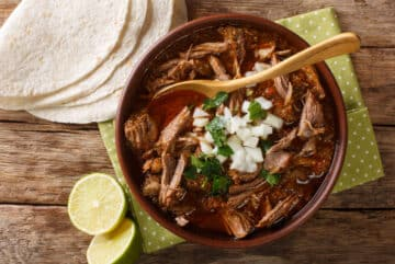 Beef Birria in Adobo sauce top down picture with tortillas and limes on the side.