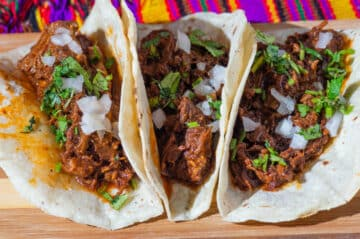 3 Birria tacos folded in half and served side by side on a wooden platter