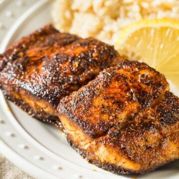 Blackened Mahi Mahi served on a white plate with rice, asparagus, and lemon slices.