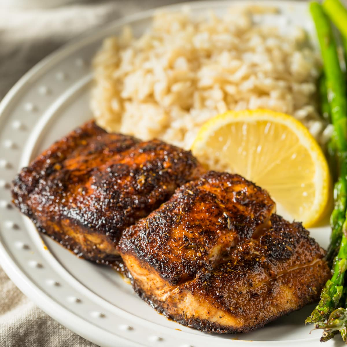 Blackened Mahi Mahi served on a white plate with rice, asparagus, and lemon slices.