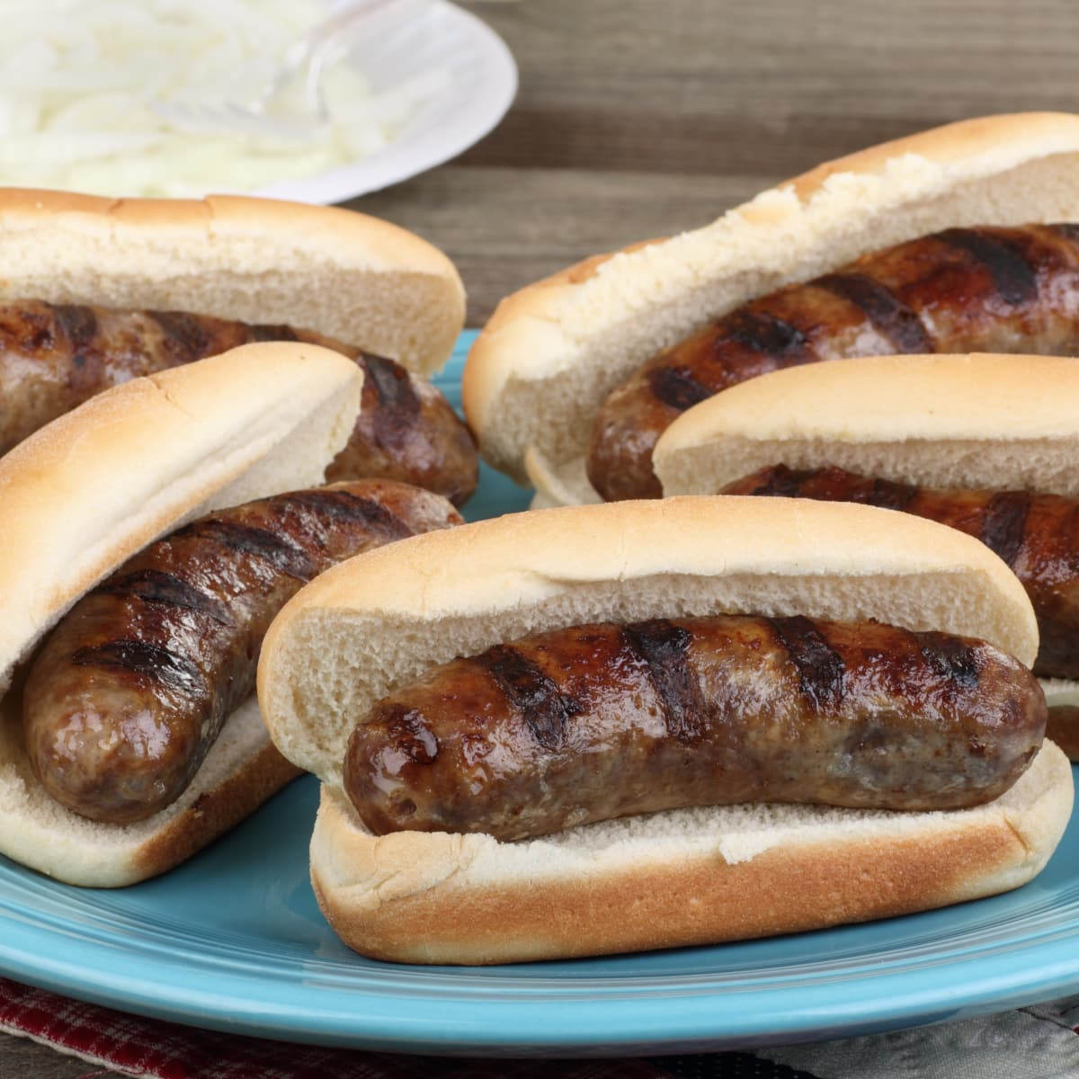beer brats served on toasted buns with sliced onions served on a blue plate