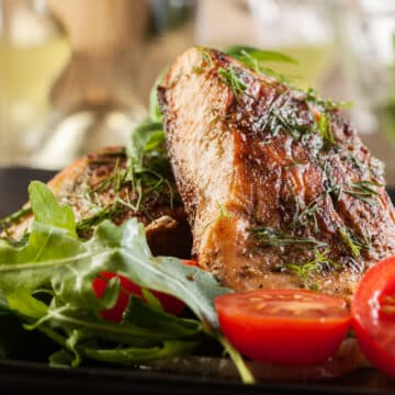 Broiled salmon fillets with golden brown crust and herb seasonings. Served with leafy greens and halved small tomatoes.