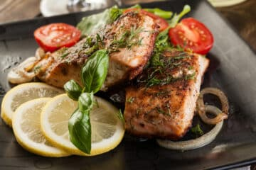 2 Broiled salmon fillets served on a dark plate with lemon slices and halved small tomatoes as garnish. Top down view.
