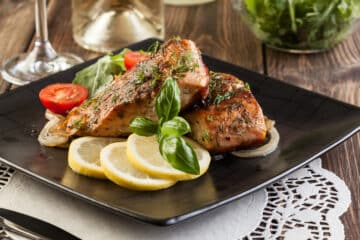 2 Broiled salmon fillets served on a dark plate with lemon slices and halved small tomatoes as garnish. Side view.