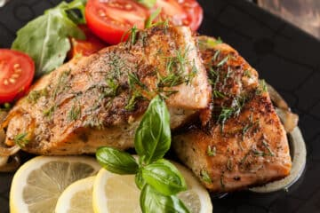 Broiled salmon with basil, citrus, and red pepper flakes top down view.
